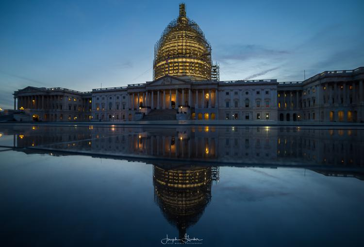 The United States Capitol Building just after sunset reflects in the skylight's of the visitor center