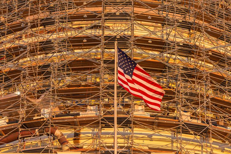 The flag of the United States of America flies in front of the scaffodling for the United States Capitol dome restoration project