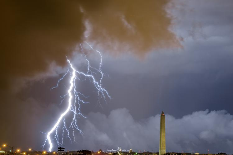 A lightning bolt seemingly hits near the Washington Monument as severe storms move through the Washington, DC metro area