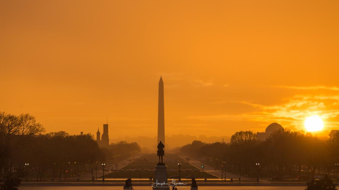 An orange sky appears, with the Washington Monument off in the distance, after rain storms pass through the DC area