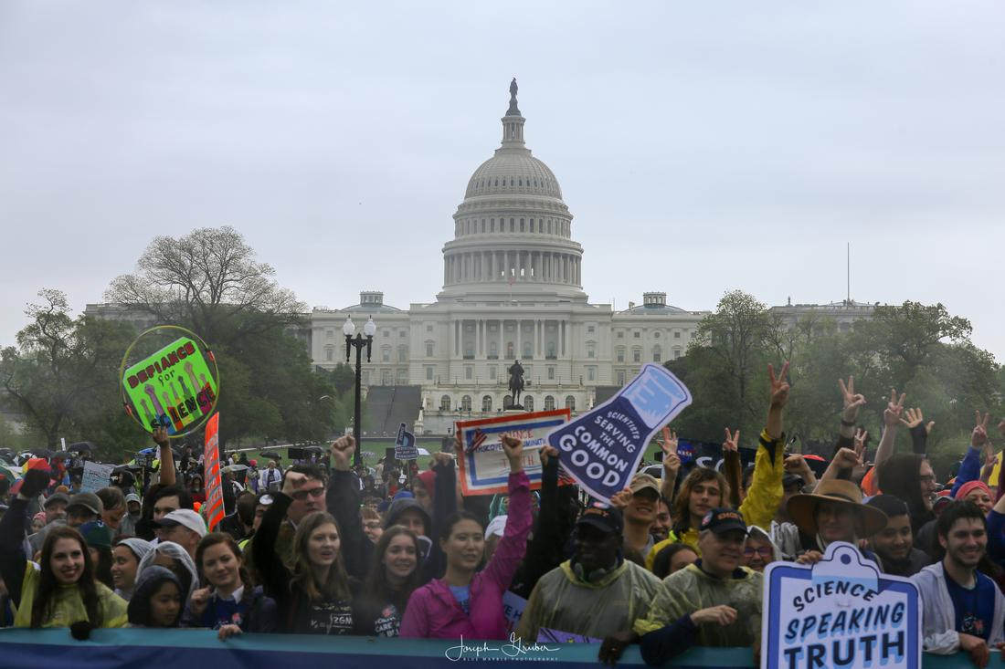 Hundreds of demonstrators march in front of the United States Capitol with signs in support of science held high