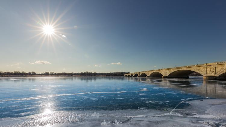 The sun shines overhead on a ice covered, frozen Potomac River