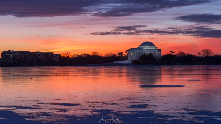 Colors are cast in the sky at sunrise over a frozen Tidal Basin and Jefferson Memorial in Washington, D.C.