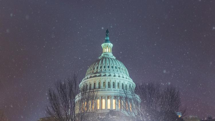 Snow flakes fall around the United States Capitol Building dome during a DC snowstorm
