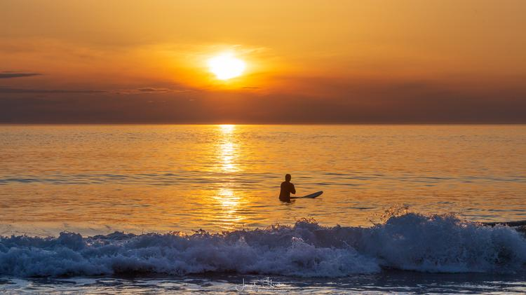 A surfer sitting on their surfboard waits in the water to catch one last wave before the sun sets