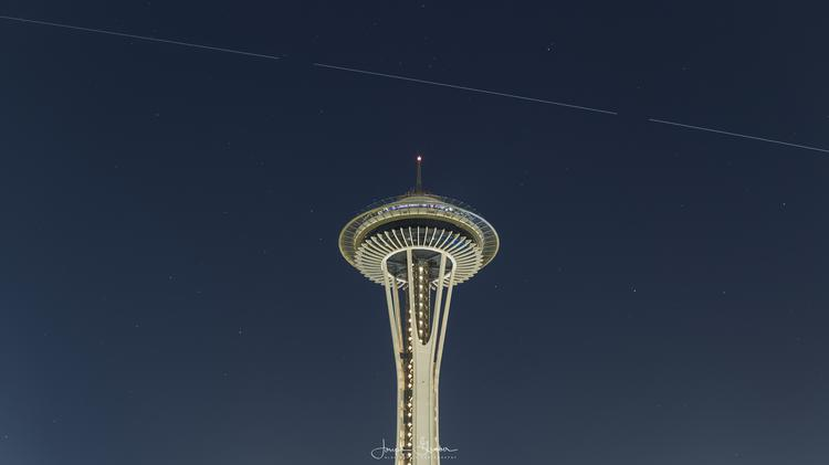 The International Space Station passes high above the Space Needle in Seattle amidst a background of stars in the night sky