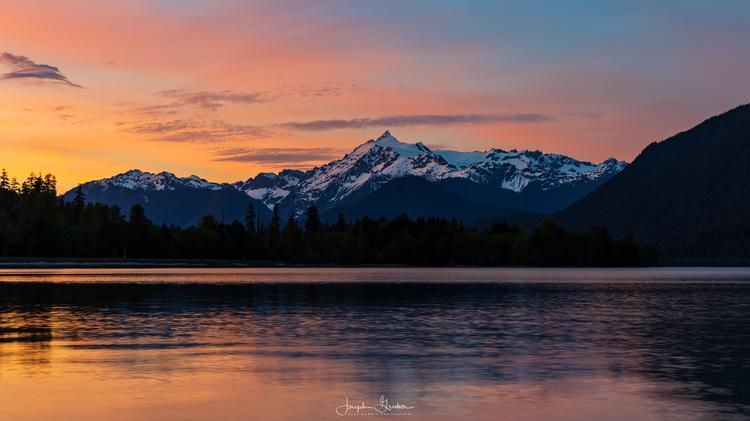 The sky glows pink as the sun sets behind Mt Baker and Baker Lake in the Pacific Northwest