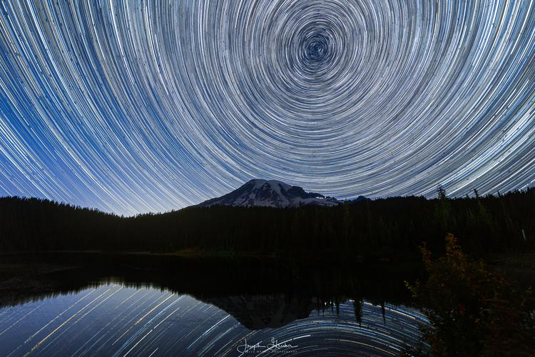 Hundreds of stars and planets rotate around the North Star, Polaris, above Mount Rainier with the reflection of both seen in Reflection Lake