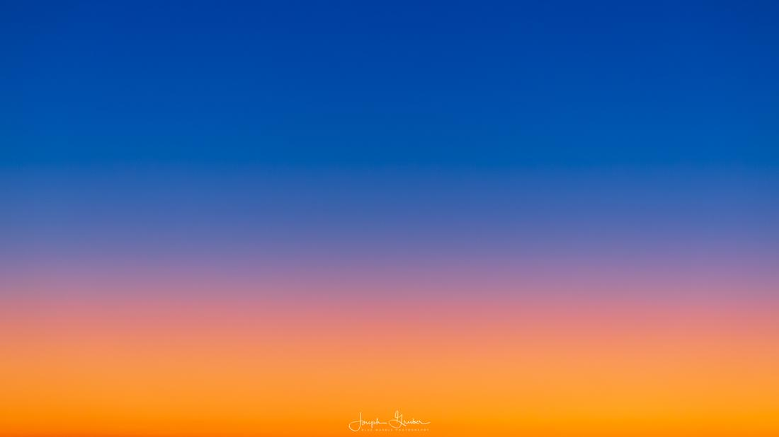 Bright orange, purple and blue colors fill the sky from the horizon to the heavens at sunrise in Denver