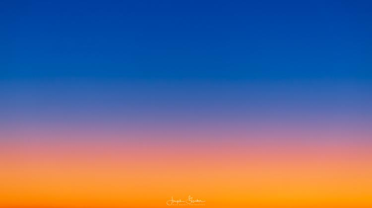 Vivid sunrise over the flatness of the Plains from the horizon to the sky with a spectrum of orange, yellow, and blues
