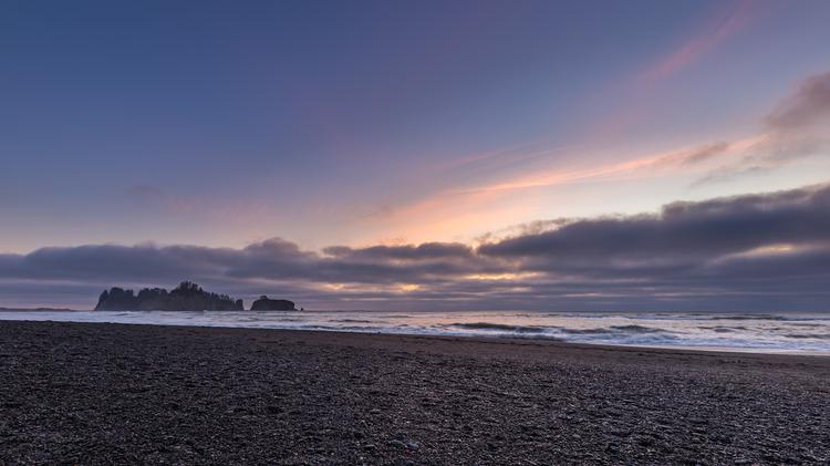 Dusk along the Pacific coastline as waves crash along the rocks and beach with pink and purple colors bright in the sky
