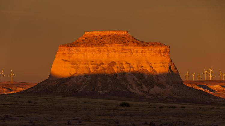 Bright sunlight shining on the east Pawnee Butte in the Pawnee National Grassland as the shadows of sunset begin to creep up the butte