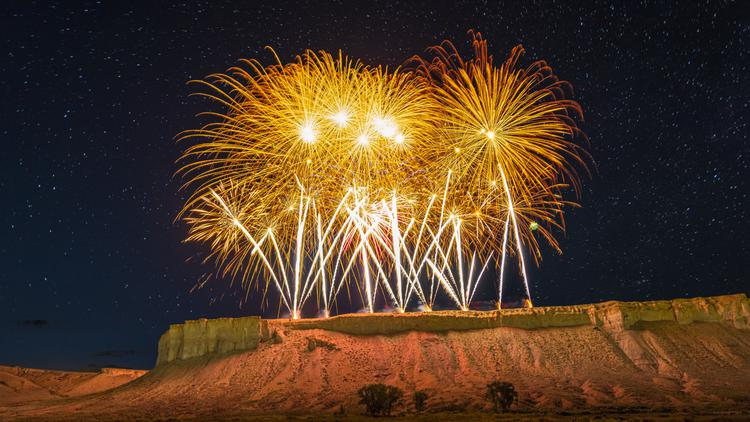 Stars and fireworks light up the night sky and rugged cliffs during Fourth of July festivities in Colorado's high country