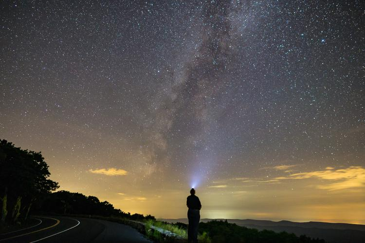Joseph Gruber looking up at the night sky as the Milky Way shines bright overhead