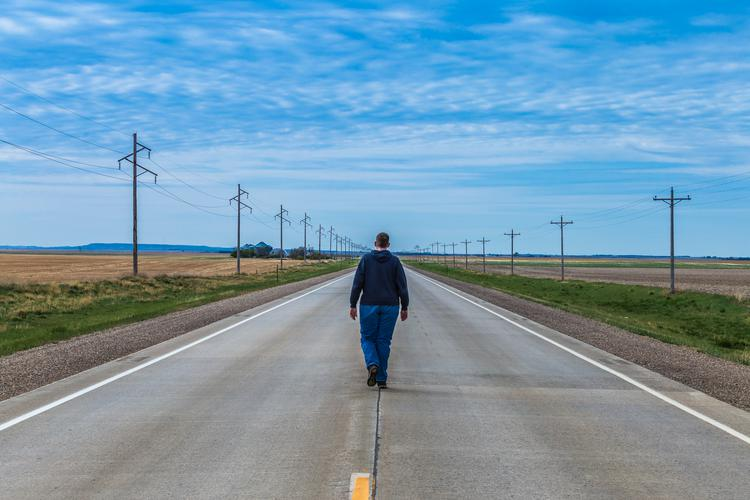 Joseph Gruber walking down a highway in South Dakota with green grass paralleling the road and blue skies overhead
